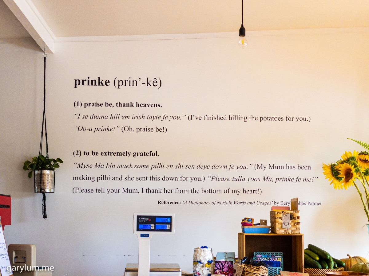 Photograph of the definition of prinke on the wall of Prinke Eco Store, Norfolk Island. prinke | to be extremely grateful | praise be, thank heavens. Gary Lum. Claire Quintal