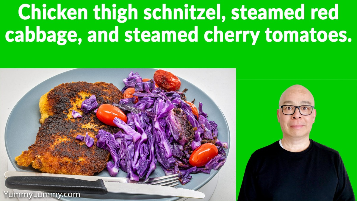 Chicken thigh schnitzel, steamed red cabbage, and cherry tomatoes