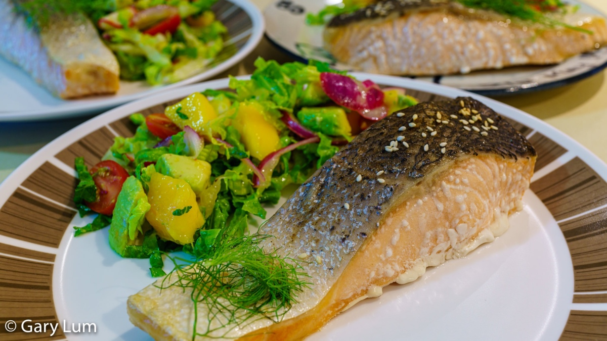 Baked salmon with pickled red onions, fennel, and radish in a mango and avocado salad