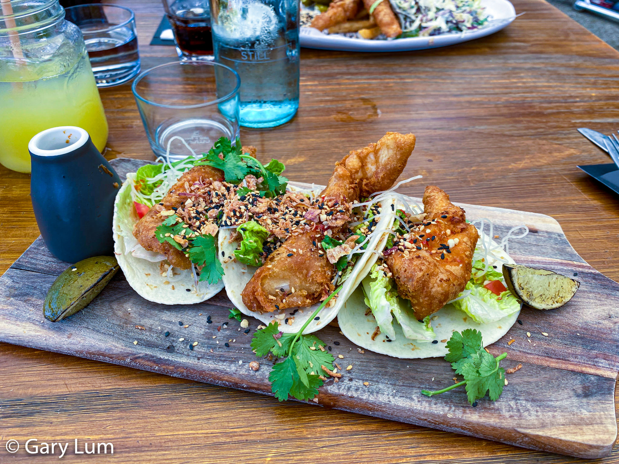 Fish tacos at Cafe Diversity. Three soft tacos with house vodka battered fish, cos leaves, vermicelli noodles, Asian herb tomato, nahm jim, toasted peanuts, and crispy fried shallots. Gary Lum.