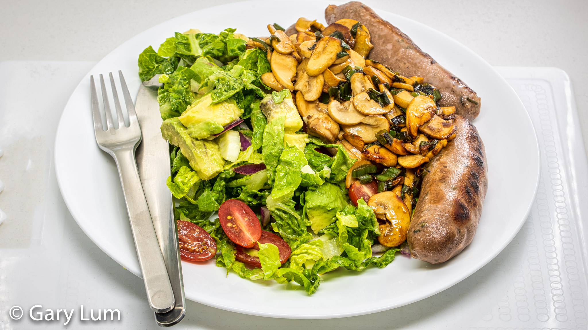 Beef sausages and avocado salad with fennel, red onion, radish and creamy mushrooms. Gary Lum.