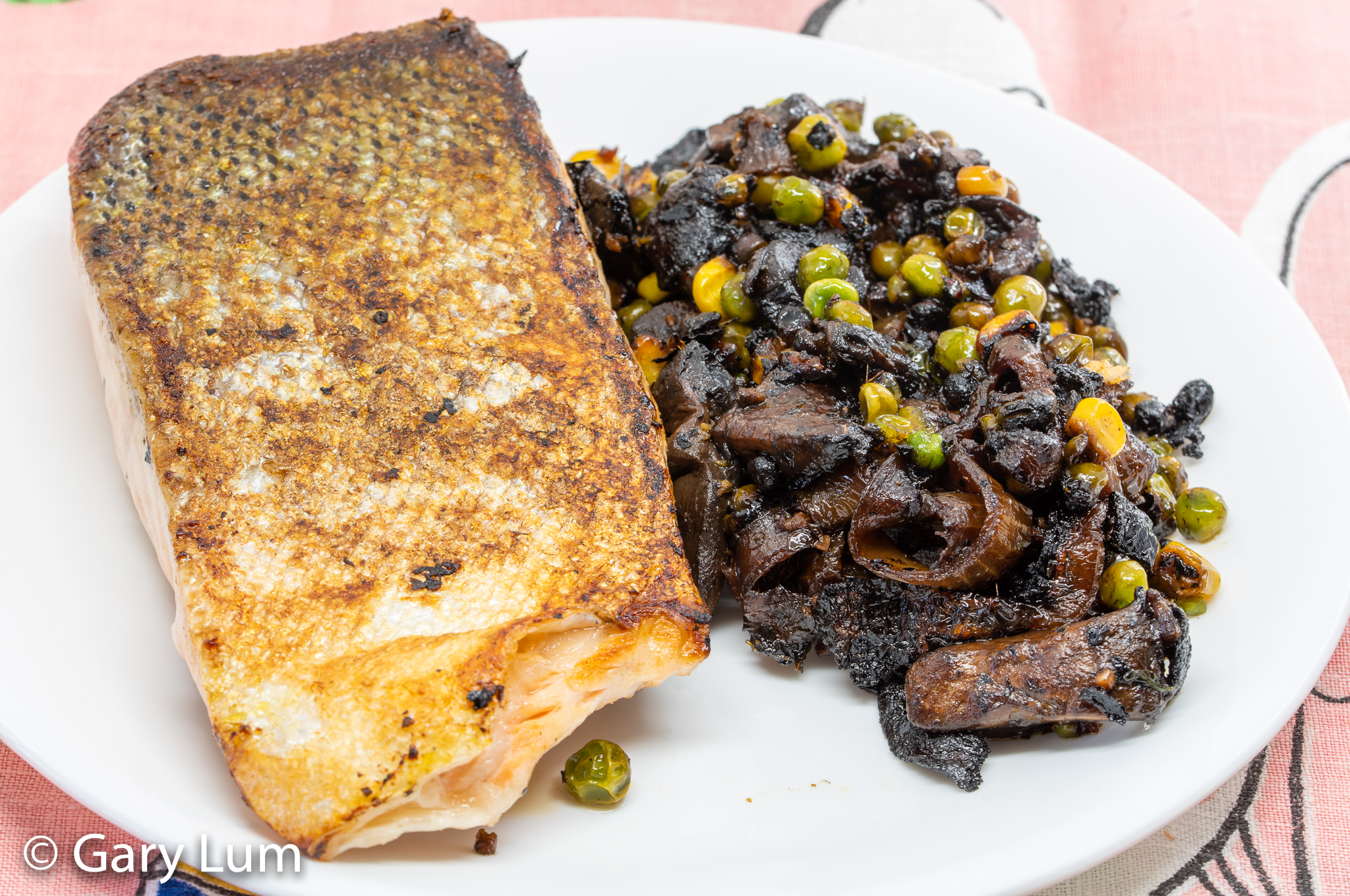 Pan-fried salmon with leftover onion and mushrooms and green and gold vegetables (peas and corn). Gary Lum.