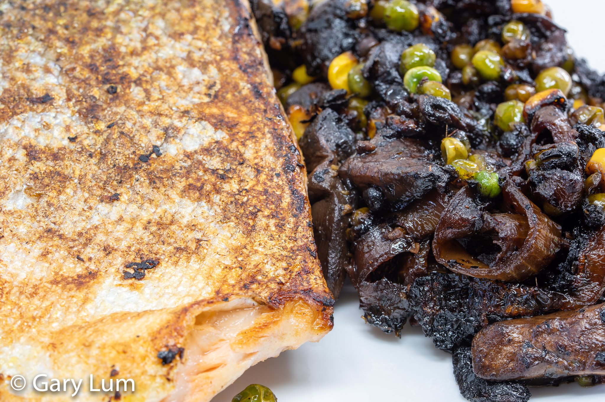 Close up. Pan-fried salmon with leftover onion and mushrooms and green and gold vegetables (peas and corn). Gary Lum.