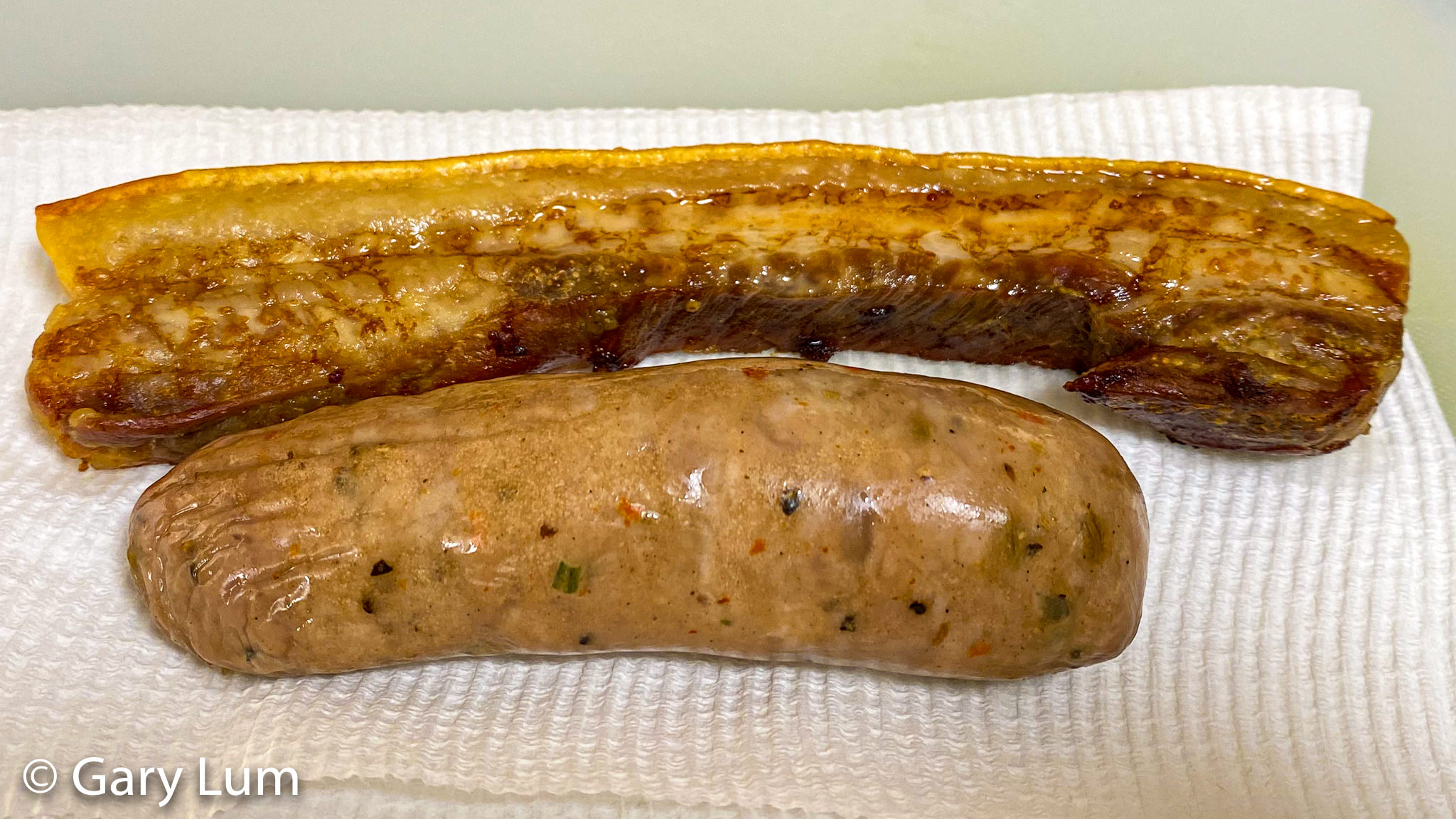 Cooked pork rasher and pork sausage. Gary Lum.