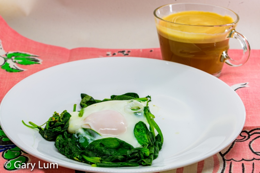Sunday breakfast. A steamed egg with wilted spinach and a cup of Nespresso™ coffee made with full cream. Gary Lum.