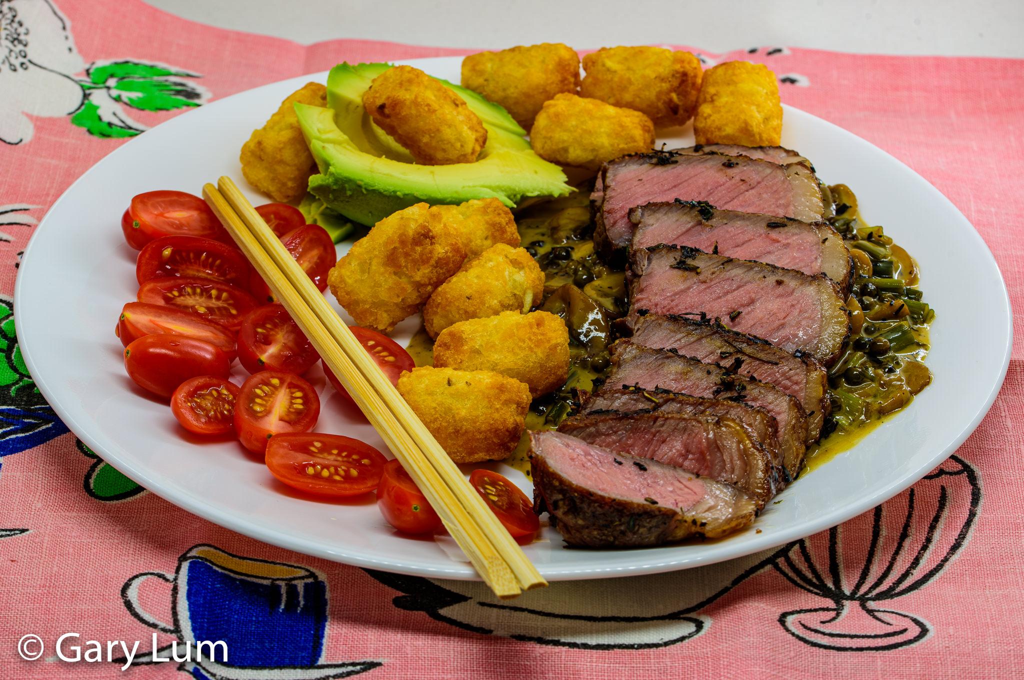 Reverse seared Porterhouse steak with green peppercorn and mushroom sauce served with potato gems, avocado, and cherry tomatoes. Gary Lum.