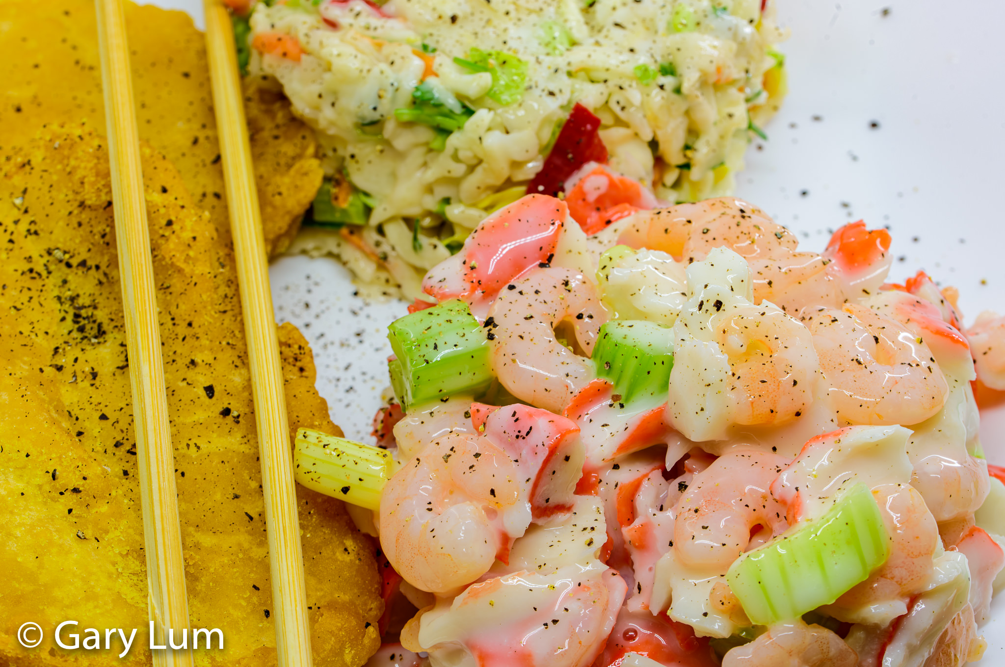 Close up. Takeaway potato scallops, seafood salad, and coleslaw. Gary Lum.