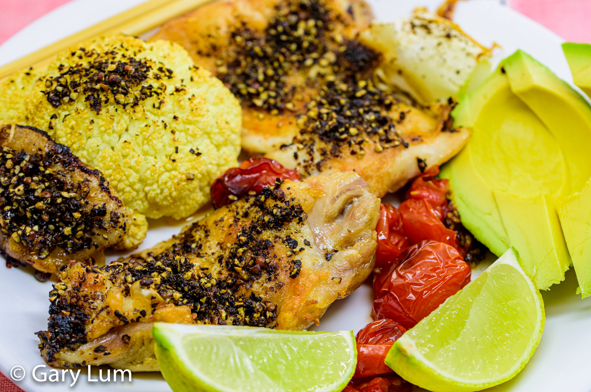 Close up. Deboned chicken thigh and drumstick with cauliflower, tomatoes, and avocado. Gary Lum.