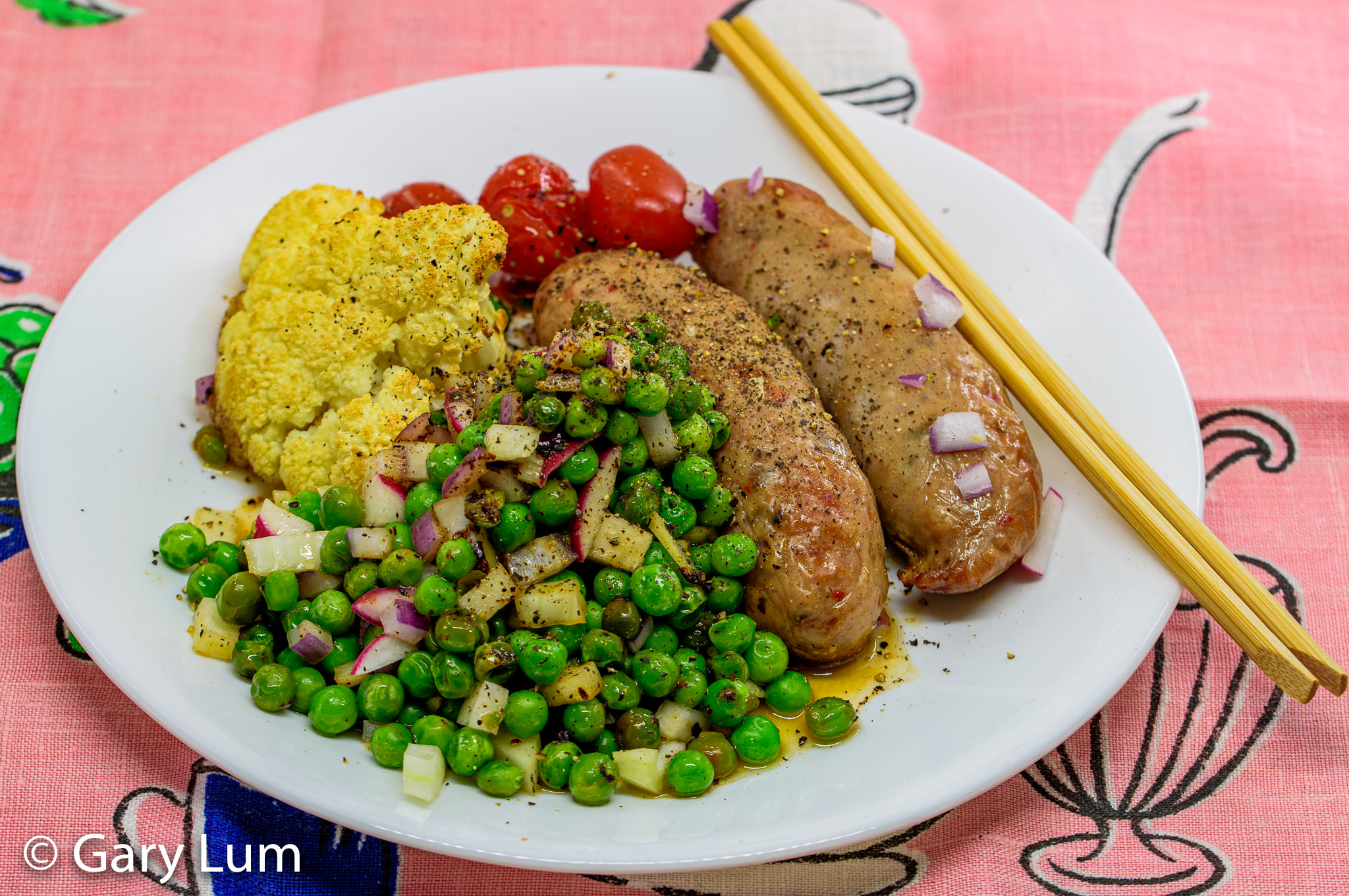 Oven-baked pork sausages, cauliflower, peas, and cherry tomatoes. Gary Lum.