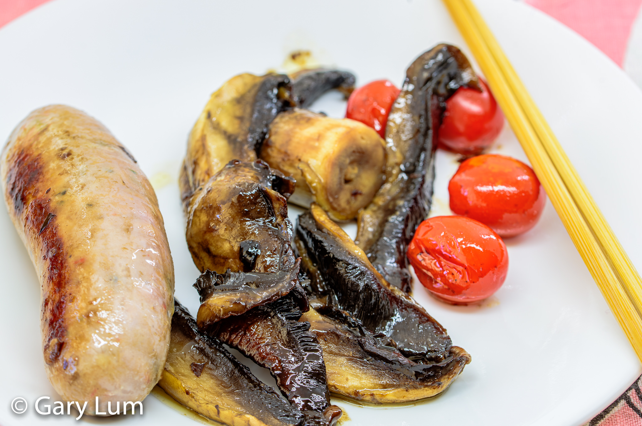 Close up. Pork sausage with mushroom and cherry tomatoes. Gary Lum.