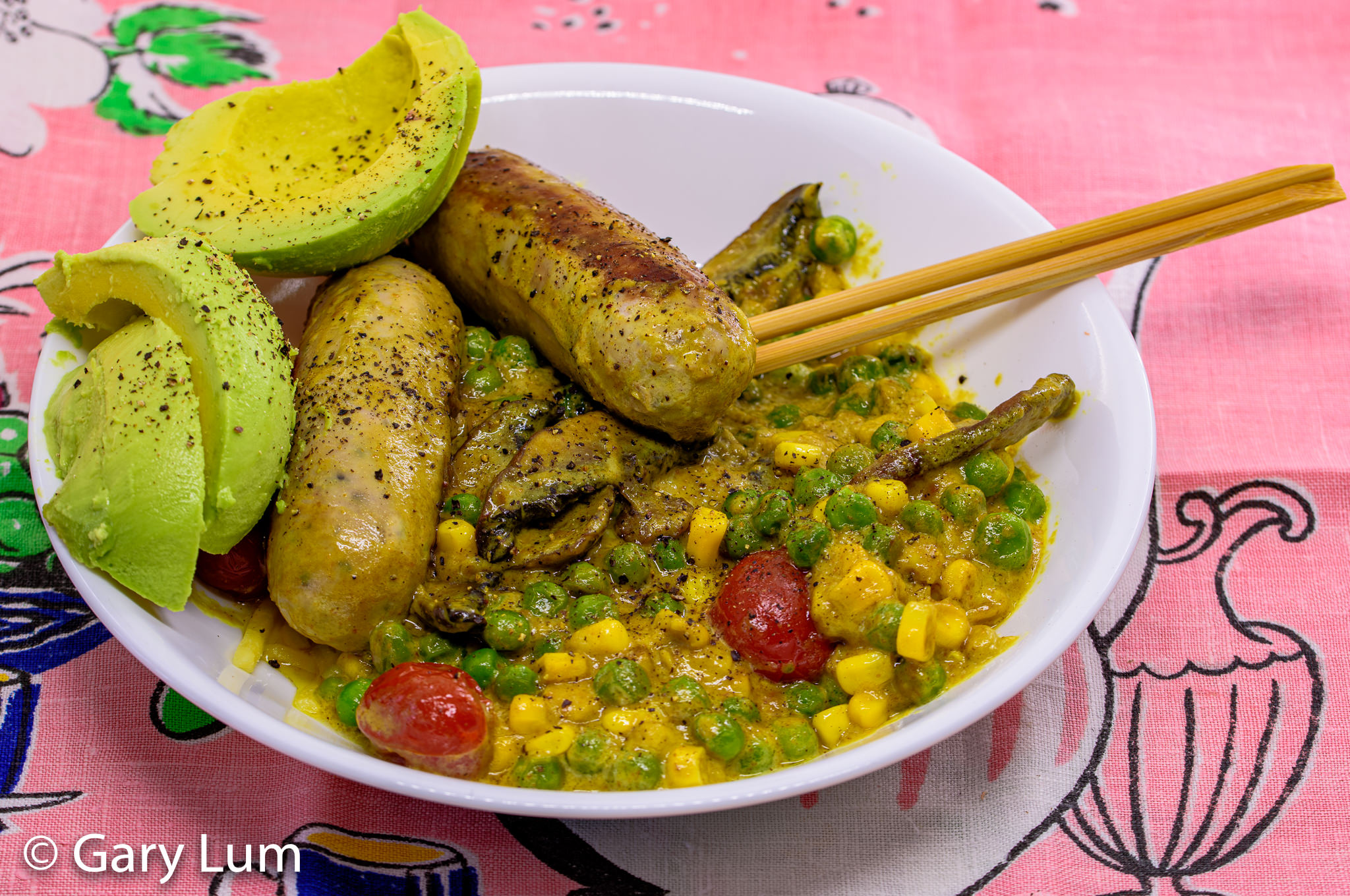 Curry pork sausages with coconut cream mushroom peas corn cherry tomatoes and an avocado. Gary Lum.