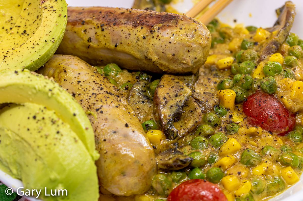 Close up. Curry pork sausages with coconut cream mushroom peas corn cherry tomatoes and avocado. Gary Lum