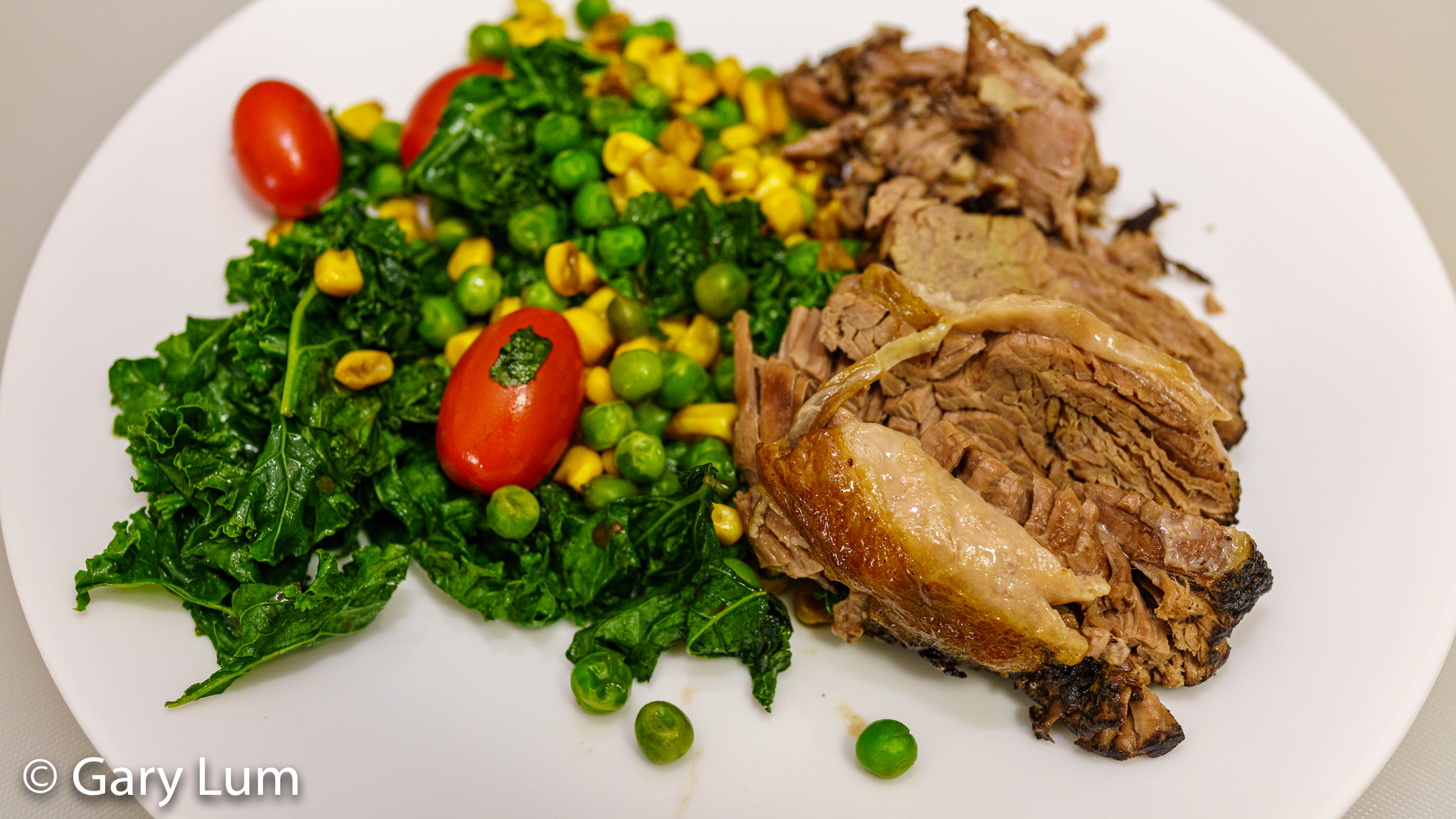 Slowly cooked lamb leg with kale, peas, corn, and tomatoes. Gary Lum.