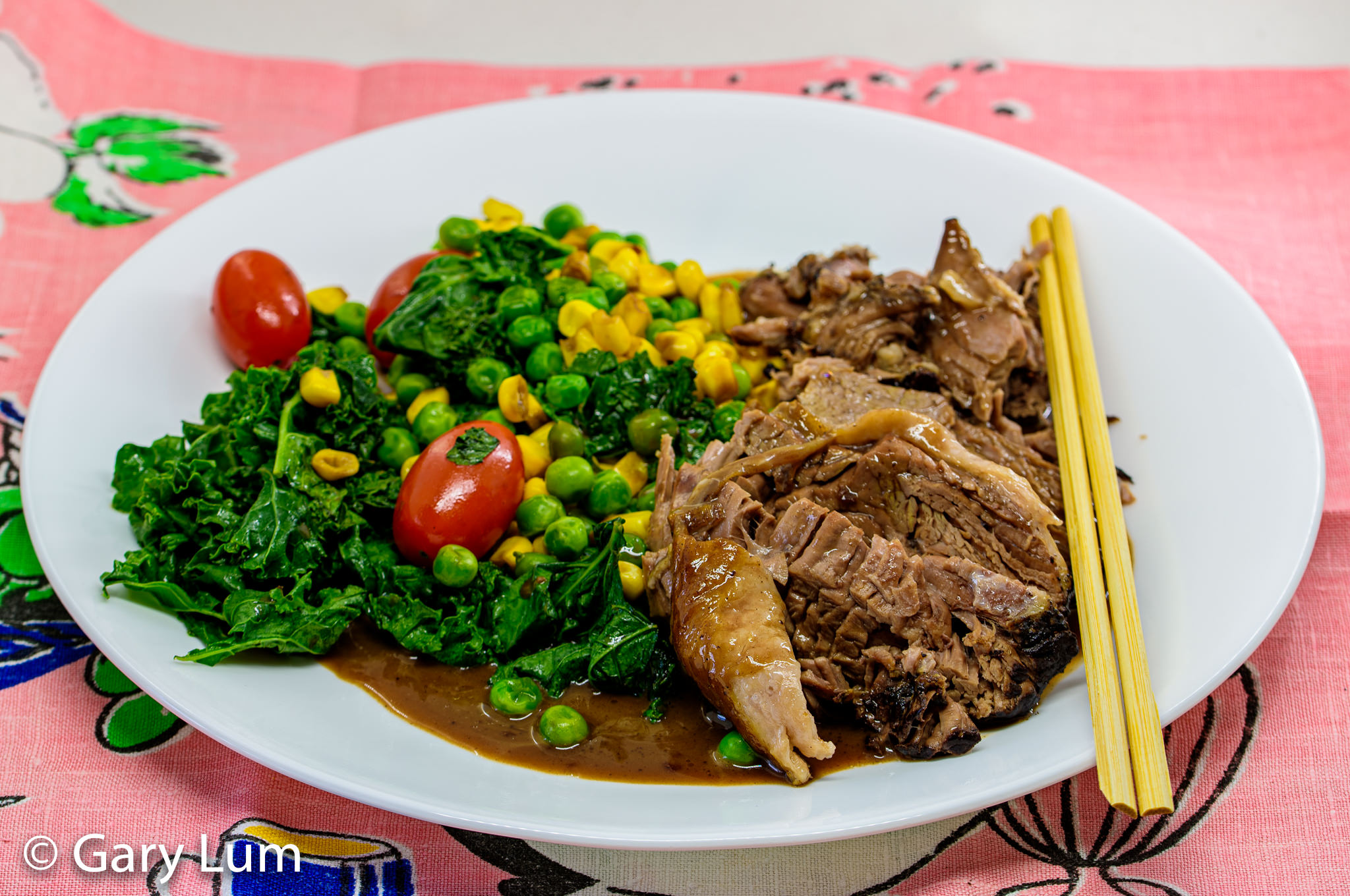 Slowly cooked lamb leg with kale, peas, corn, and tomatoes plus gravy. Gary Lum.