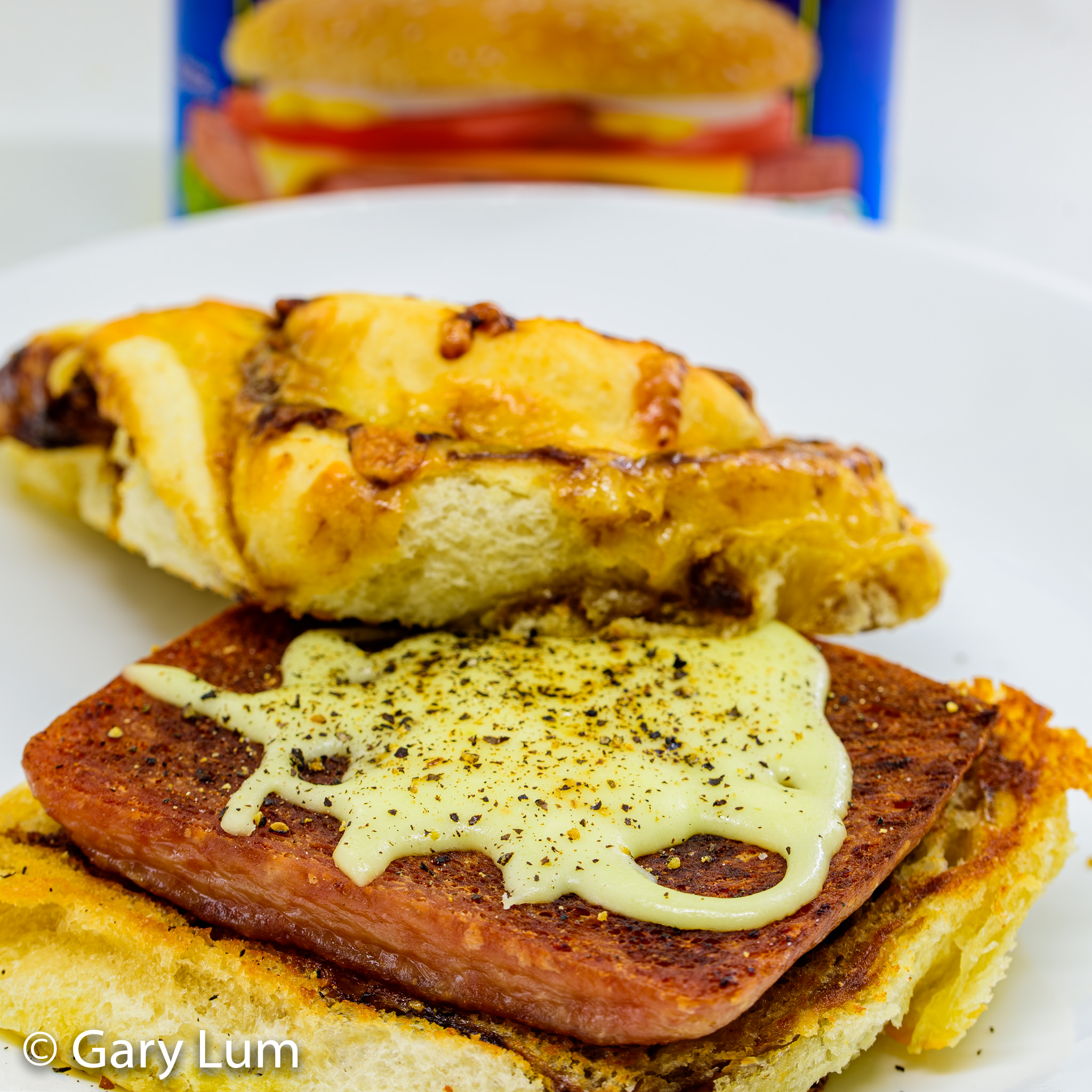 Close up. Pan-fried Spam with melted Mozzarella on a Coles Cheesy Vegemite Scroll. Gary Lum.