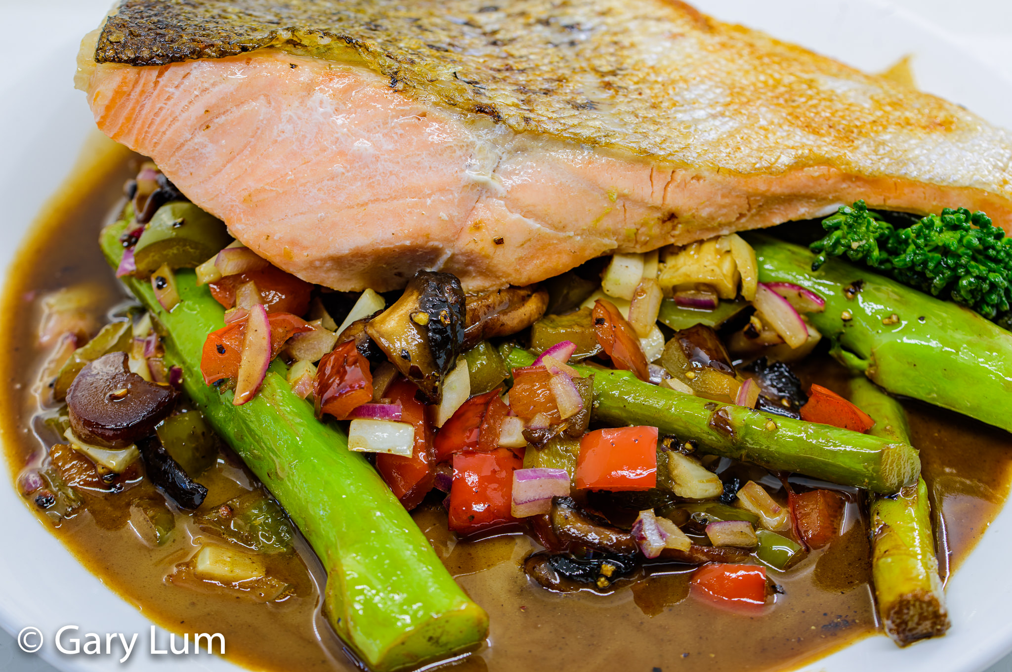 Close up. Pan-fried salmon with broccolini, asparagus, capsicum, red onion, fennel, and leftover gravy. Gary Lum.