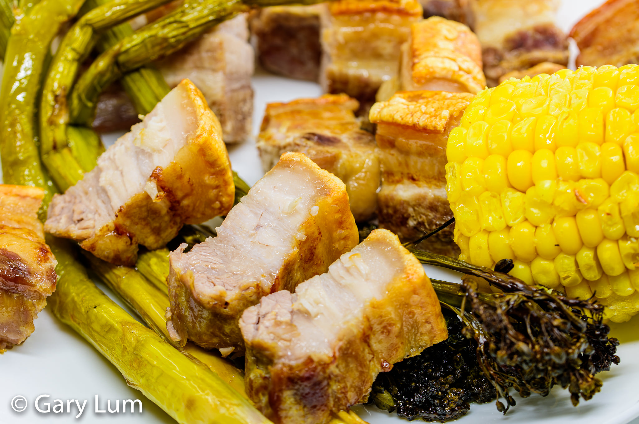 Close up. Oven-baked pork belly with broccolini, asparagus, and corn. Gary Lum.