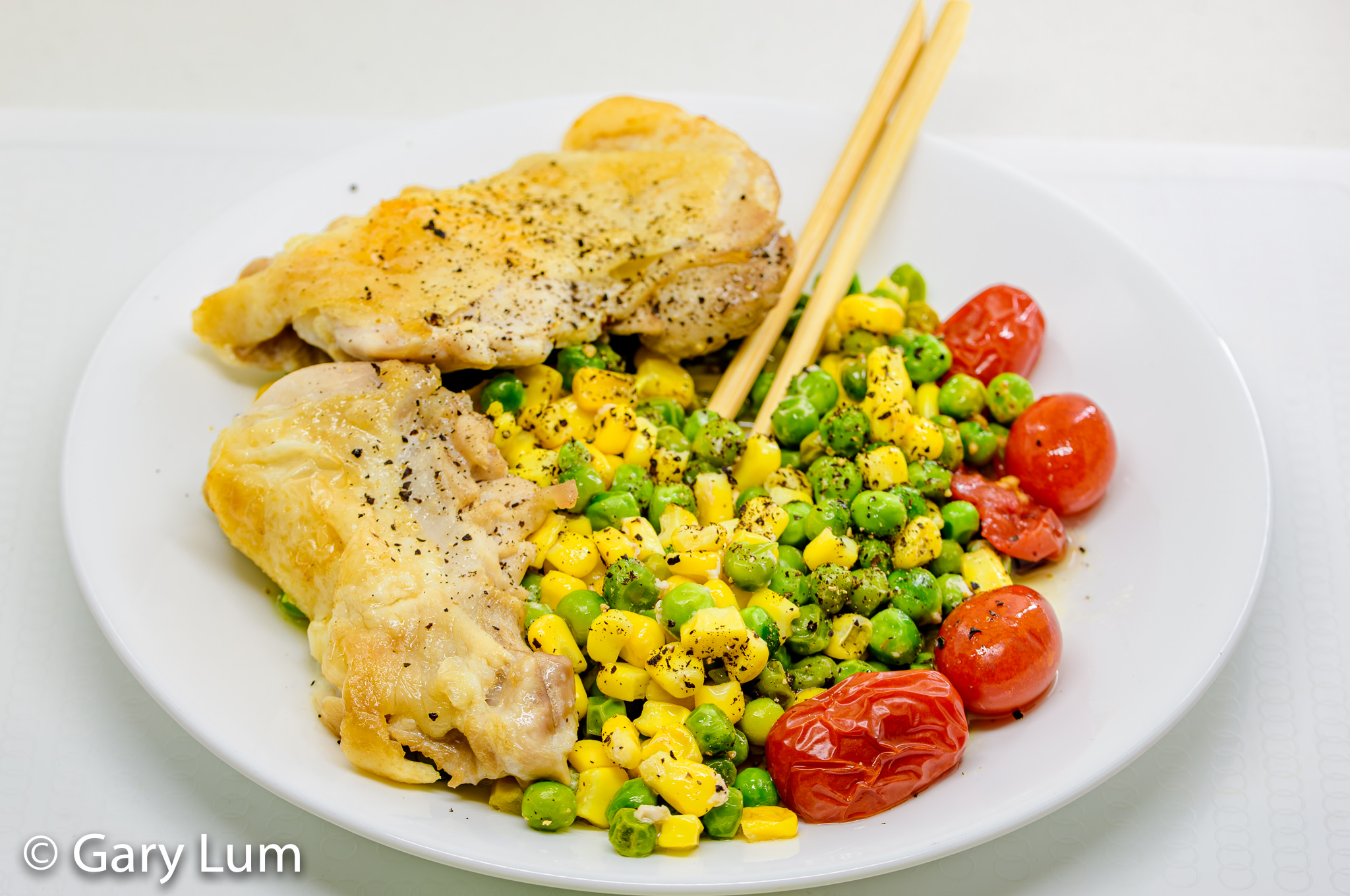 Deboned oven cooked chicken thigh and drumstick with peas, corn, and cherry tomatoes. Gary Lum.