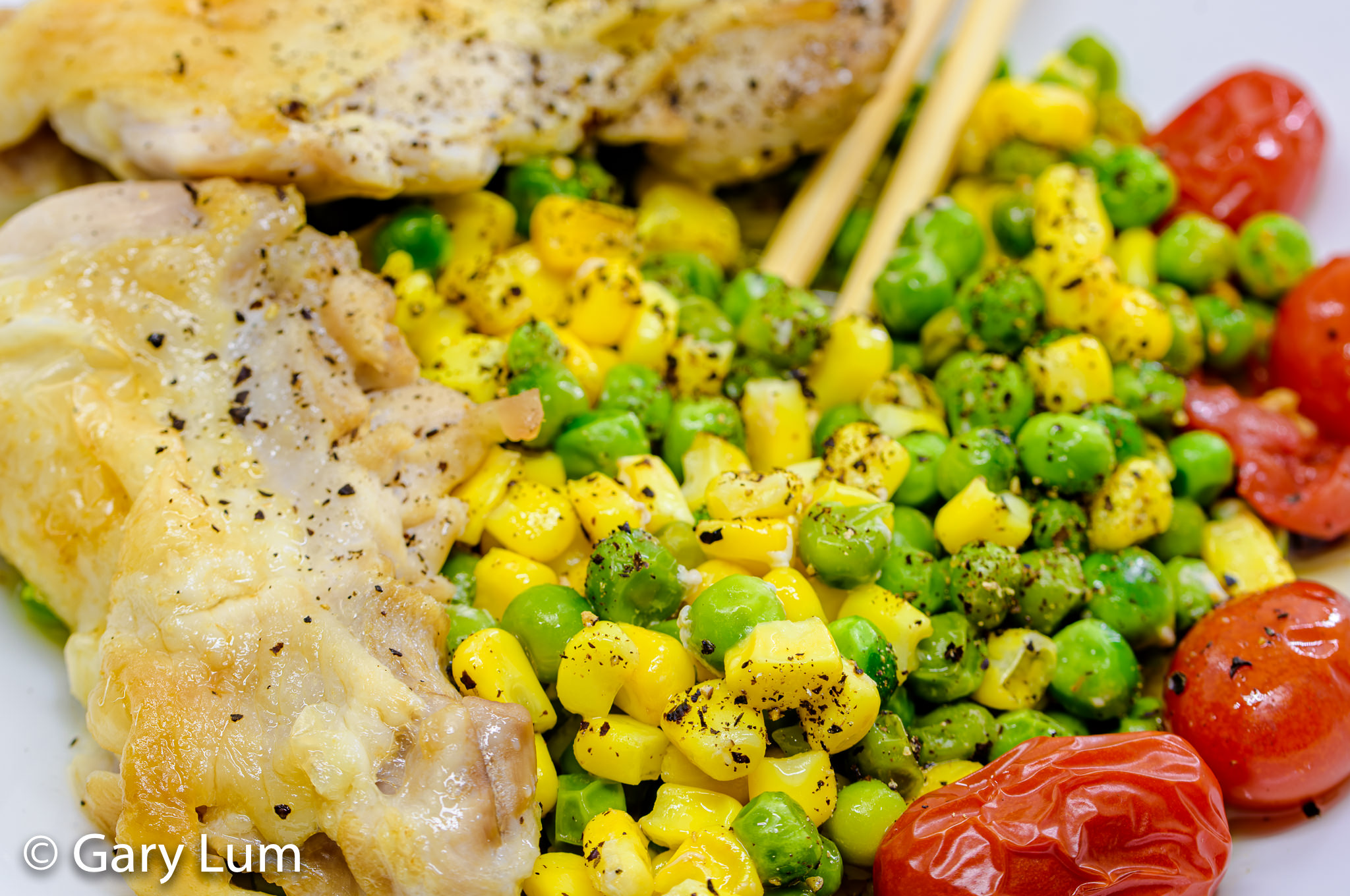Close up. Deboned oven cooked chicken thigh and drumstick with peas, corn, and cherry tomatoes. Gary Lum.
