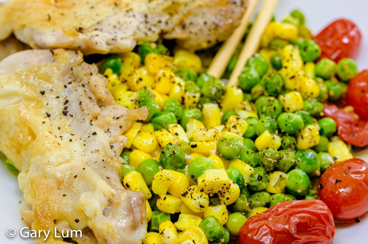 Deboned oven cooked chicken thigh and drumstick with peas, corn, and cherry tomatoes