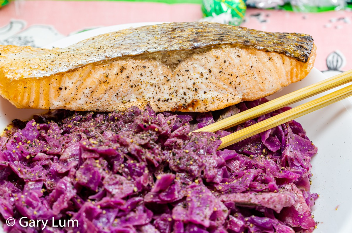 Close up. Oven-cooked salmon with leftover sous vide duck and curry red cabbage.