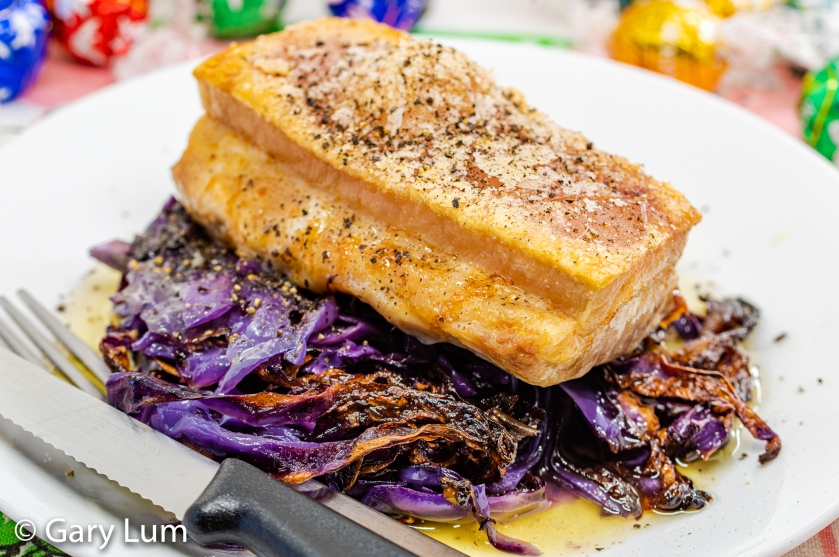 Close up. Oven cooked pork belly and red cabbage with butter.