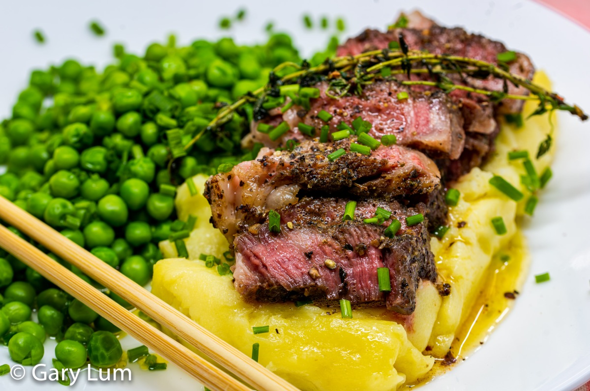 Close up. Sous vide medium-rare beef spinalis dorsi with burnt butter and thyme on a bed of potato mash and served with baby green peas.