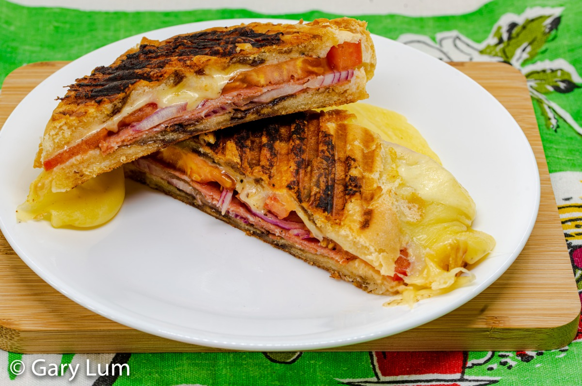 Cheesy Vegemite Toastie with salami, red onion, tomato, and mozzarella and Colby cheeses with a crispy mayonnaise lubricatedcrust