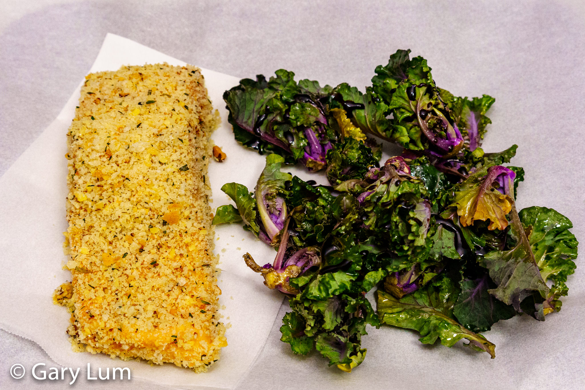 Raw crumbed salmon and seasoned kale sprouts.