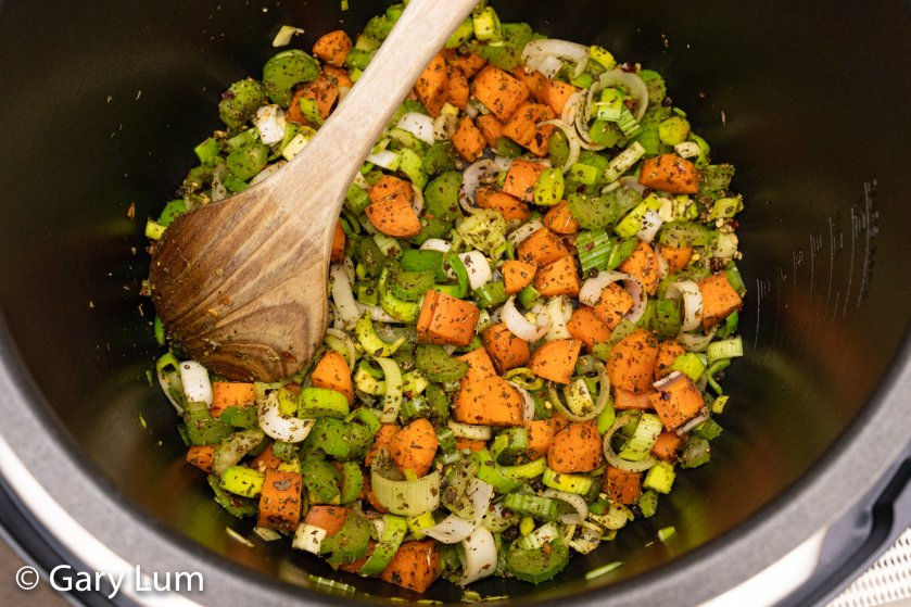Sautéing carrot, celery, leek, and dry herbs with hot red chilli flakes in the Fast Slow Cooker.