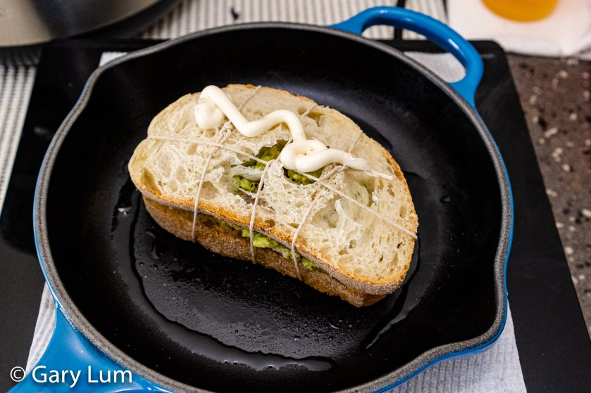 Italian bread with Mersey Valley pickled onion cheese, sliced tomato, and smashed avocado bound with cooking twine being grilled in a cast iron skillet on an induction hob