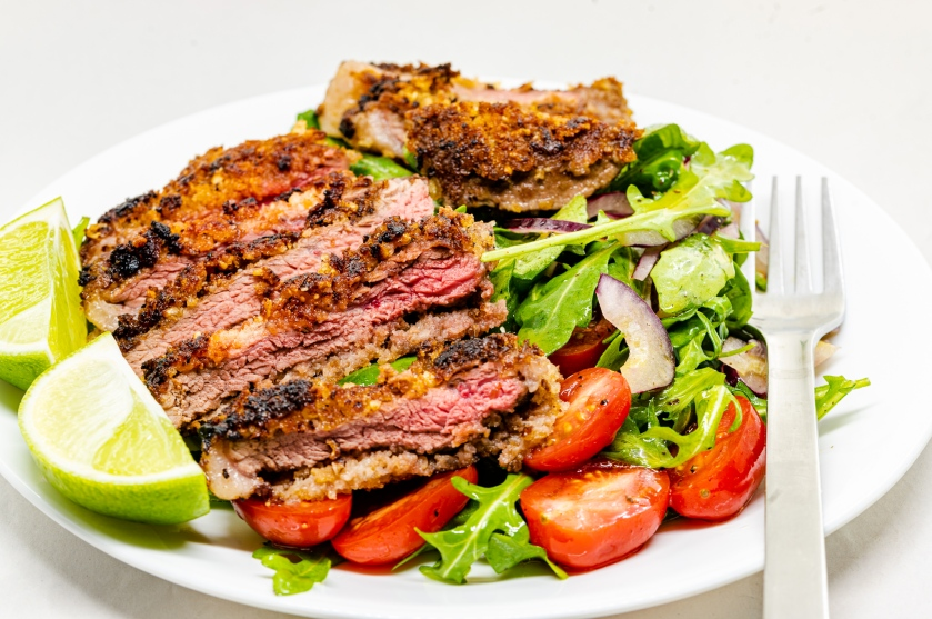 Crumbed, nutted, and beaten rump steak with rocket salad