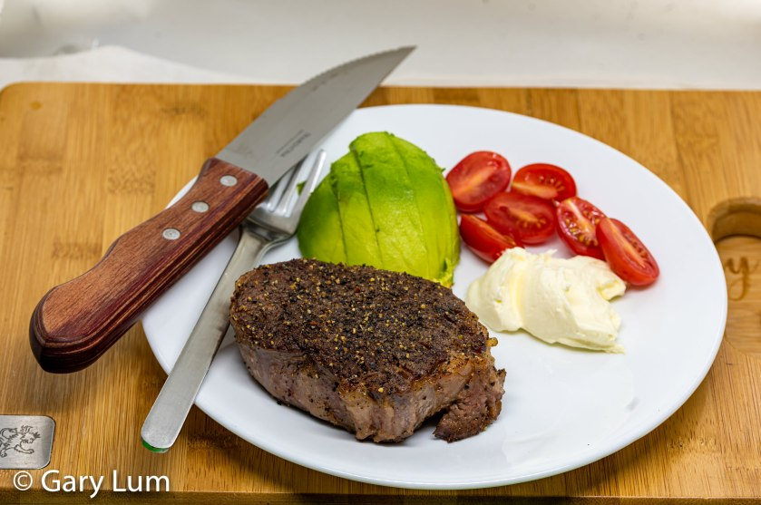 Sous vide Angus beef scotch fillet steak with avocado, cherry tomatoes, and sour cream.