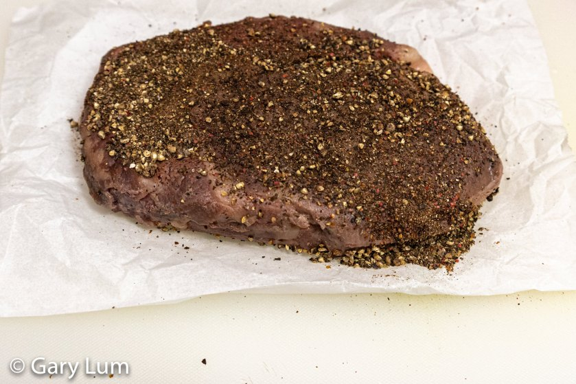 Scotch fillet steak out of the sous vide water bath which has been seasoned with freshly ground black whole peppercorns