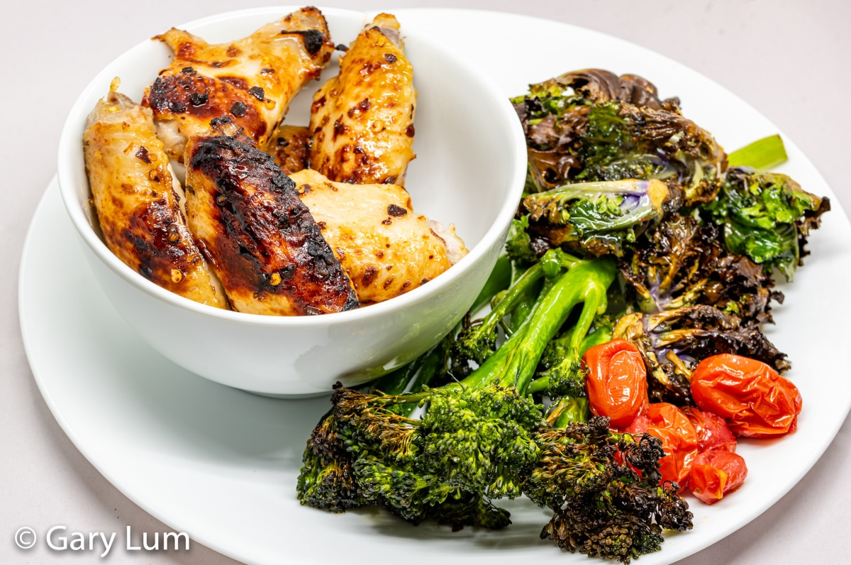 Oven-cooked chicken wings, broccolini, kale sprouts, and cherry tomatoes