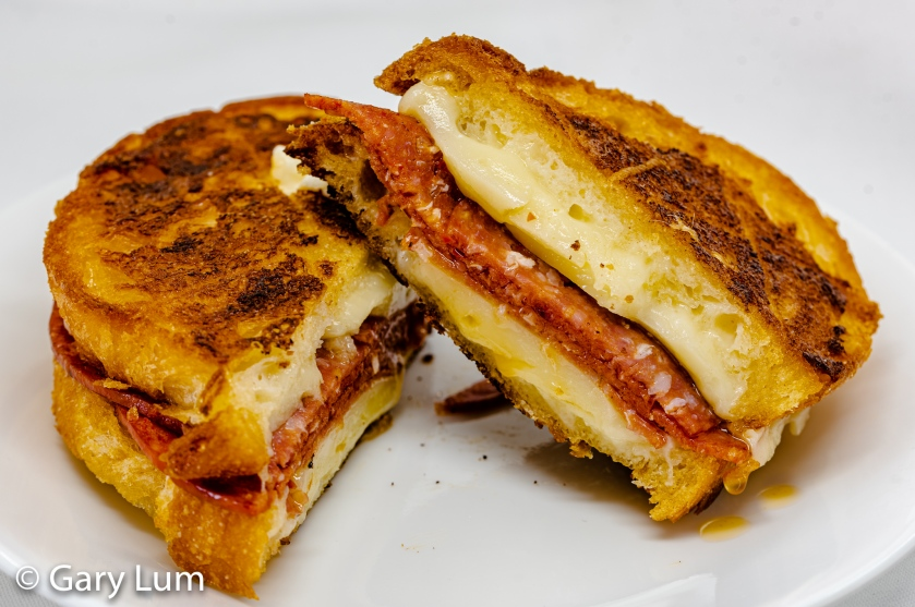 Provolone piccante, salami and pepperoni grilled cheese toastie cut diagonally