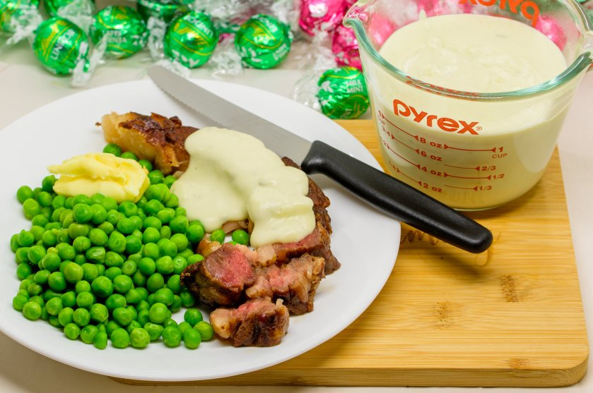 Reverse seared scotch fillet steak with blue cheese sauce and baby green peas